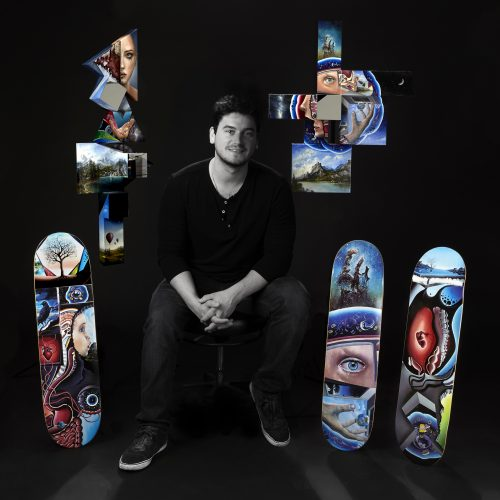 Steve sits with his canvas pieces on the wall above his new skateboard art..
